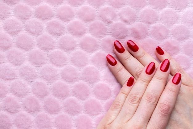 Vrouwelijke handen met mooie manicure - rode glitter nagels op roze pluizige muur met kopie ruimte