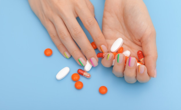 Vrouwelijke handen met mooie moderne manicure en pillen
