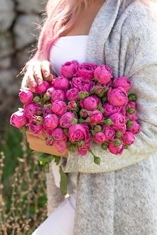 Vrouwelijke handen met mooie roze rozen en pioenrozen