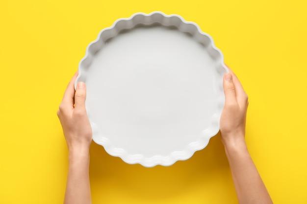 Vrouwelijke handen met ovenschaal op kleur achtergrond