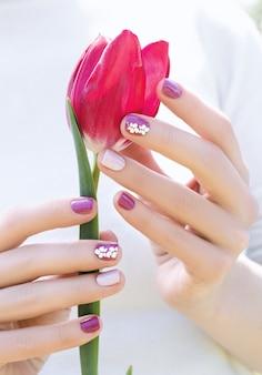 Vrouwelijke handen met paarse nagel ontwerp met mooie roze tulp.