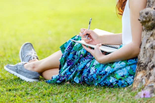 Vrouwelijke handen met pen die op notitieboekje op gras buiten schrijven