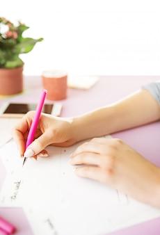 Vrouwelijke handen met pen. telefoon op trendy roze bureau.