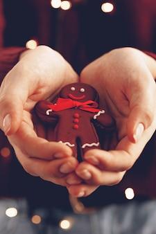 Vrouwelijke handen met peperkoek man close-up, kerst concept