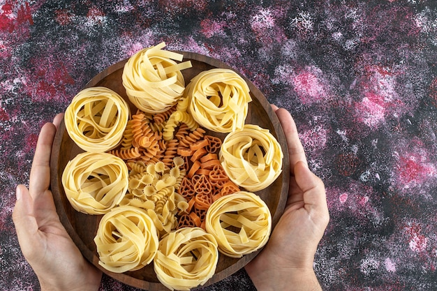 Vrouwelijke handen met plaat van verschillende macaroni.