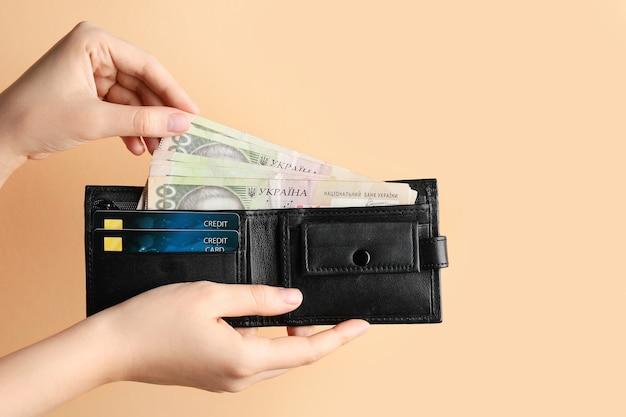 Vrouwelijke handen met portemonnee, creditcards en geld op roze