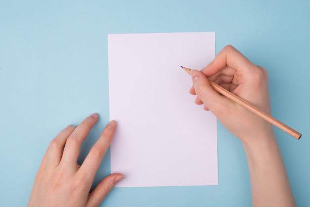 Vrouwelijke handen met potlood over wit vel papier