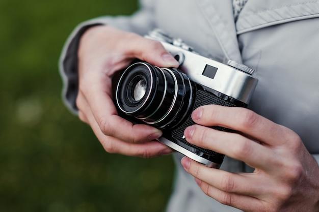 Vrouwelijke handen met retro fotocamera en corrigeert de externe afstand op straat.