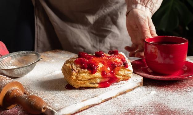 Vrouwelijke handen met rode kopje koffie in de buurt van puff bemand met pruimen of rode bessen jam op tafel.