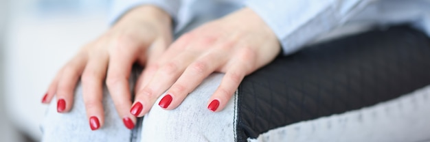 Vrouwelijke handen met rode manicure die op knieën liggen closeup