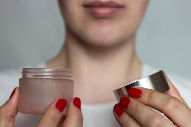 Vrouwelijke handen met rode manicure houden een open pot met room. het concept van gezichtsverzorging. selectieve aandacht