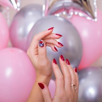 Vrouwelijke handen met rode manicurespijkers