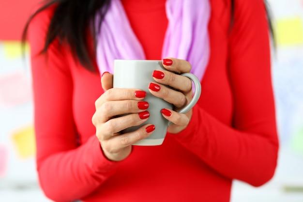 Vrouwelijke handen met rode nagels die grijze kop van koffie houden