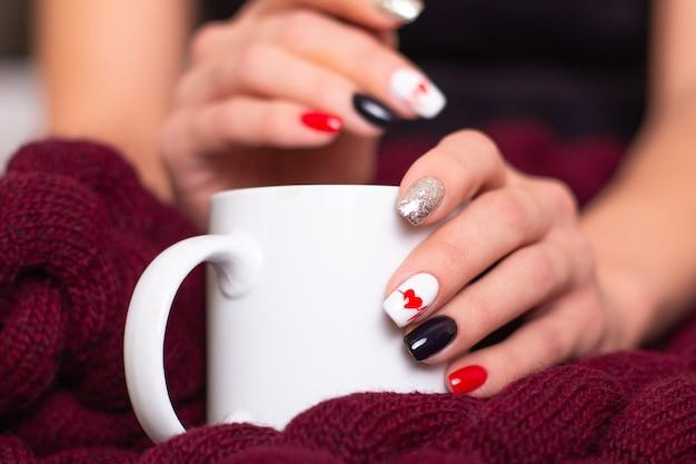 Vrouwelijke handen met romantische manicurespijkers, hartontwerp