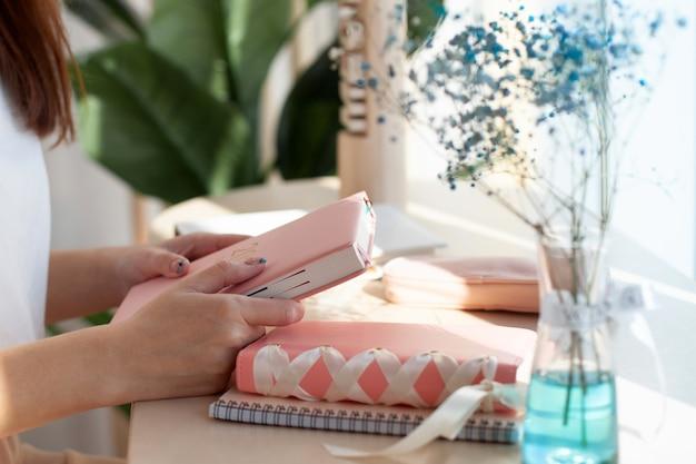 Vrouwelijke handen met roze koraalkleurig lederen dagboek terwijl ze bij een raam in café zitten