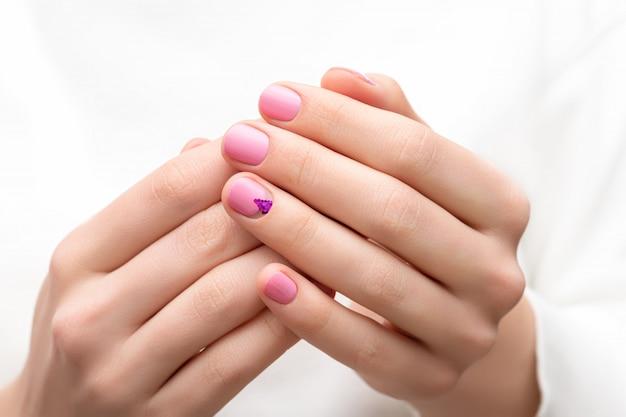 Vrouwelijke handen met roze nagel ontwerp.