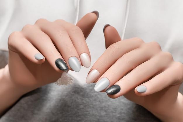 Vrouwelijke handen met roze spijkerontwerp op grijze stoffenoppervlakte.