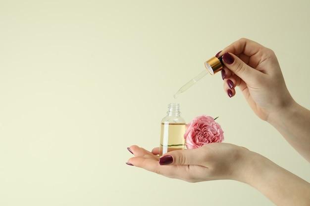 Vrouwelijke handen met rozen etherische olie op beige
