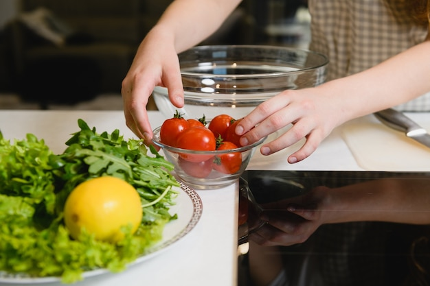 Vrouwelijke handen met salade-ingrediënten op tafel