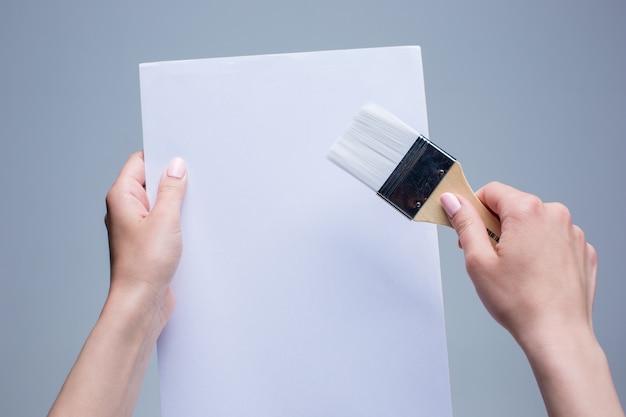 Vrouwelijke handen met schilderij penseel op wit doek