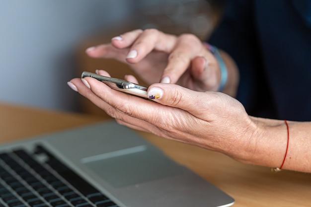 Vrouwelijke handen met slimme telefoon en computertoetsenbord, close-up