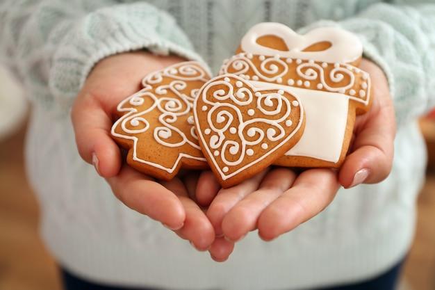 Vrouwelijke handen met smakelijke peperkoekkoekjes