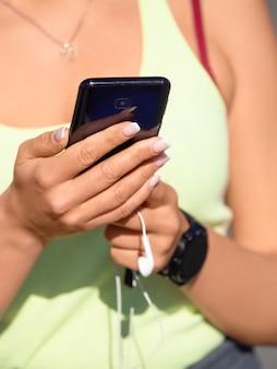 Vrouwelijke handen met smartphone close-up ze kiest muziek voor haar ochtendrun