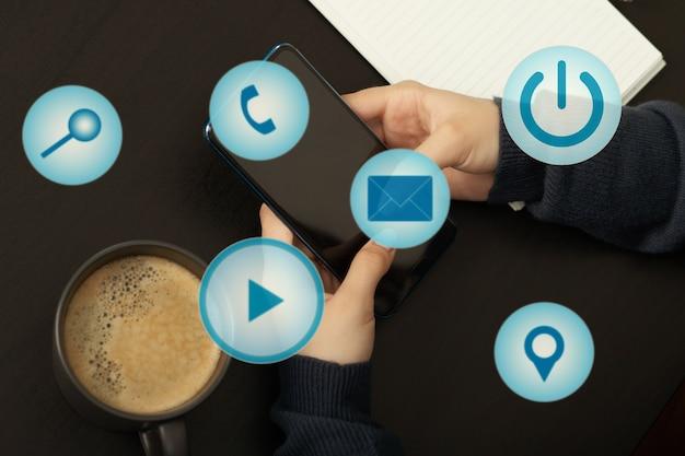 Vrouwelijke handen met smartphone met verschillende social media iconen, bedrijfsconcept
