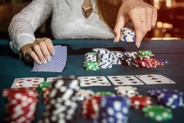 Vrouwelijke handen met speelkaarten en pokerfiches