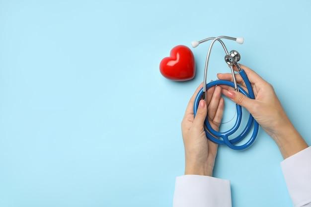Vrouwelijke handen met stethoscoop op blauw met hart