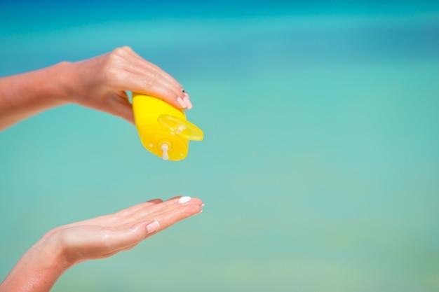 Vrouwelijke handen met suncream fles blauwe zee
