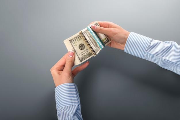Vrouwelijke handen met valutabundel. onderneemster die groot geld houdt. maandelijks inkomen van het bedrijf. die kleurrijke papieren.