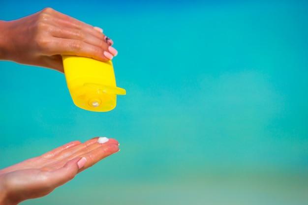 Vrouwelijke handen met van de suncreamfles blauwe overzees als achtergrond