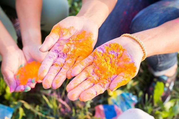 Vrouwelijke handen met veelkleurig poeder op