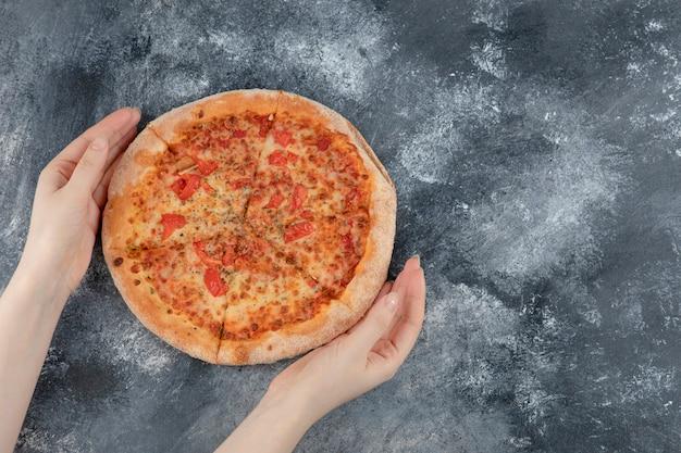 Vrouwelijke handen met verse hele pizza op marmeren oppervlak. 3d-afbeelding van hoge kwaliteit
