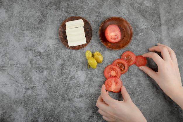 Vrouwelijke handen met verse tomaten op stenen achtergrond.