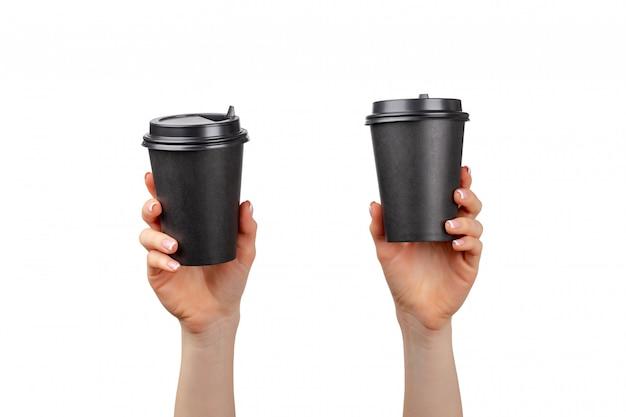 Vrouwelijke handen met wegwerp koffiekopjes