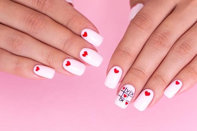 Vrouwelijke handen met witte manicure, hartenontwerp