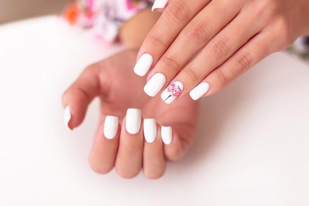 Vrouwelijke handen met zachte manicure nagels, roze gel polish, pioenrozen bloemen design