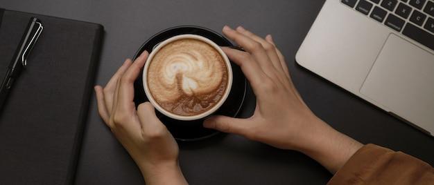 Vrouwelijke handen met zwarte kop koffie op donkere werkruimte met laptop en dagboek notebook