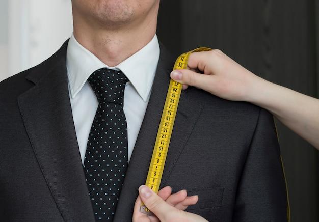 Vrouwelijke handen meten de kraag van een jas en naaien kleding