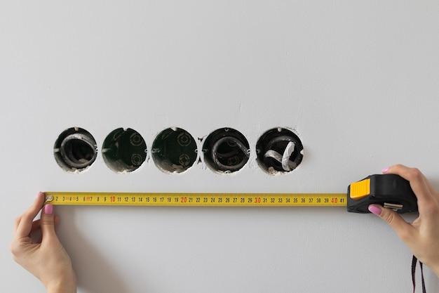 Vrouwelijke handen meten de lengte van de muur met een meetlint. hoge kwaliteit foto