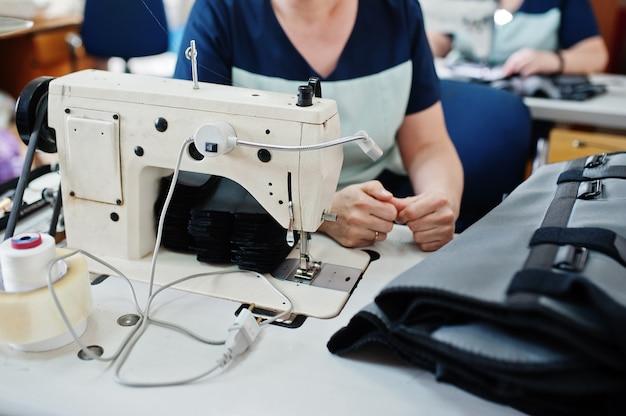 Vrouwelijke handen naaien stof op professionele productiemachine op de werkplek. naaiproces.