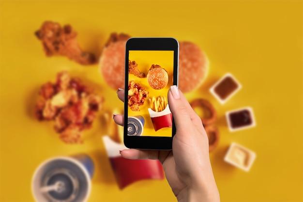 Vrouwelijke handen nemen foto van smakelijke hamburger met snacks op tafel