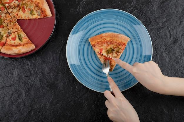 Vrouwelijke handen nemen plak van pizza uit plaat op zwarte achtergrond.