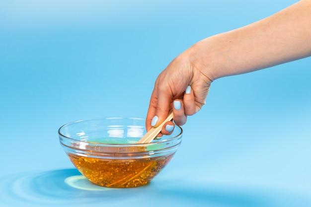 Vrouwelijke handen nemen suikerpasta voor het suikeren met een houten spatel op blauw