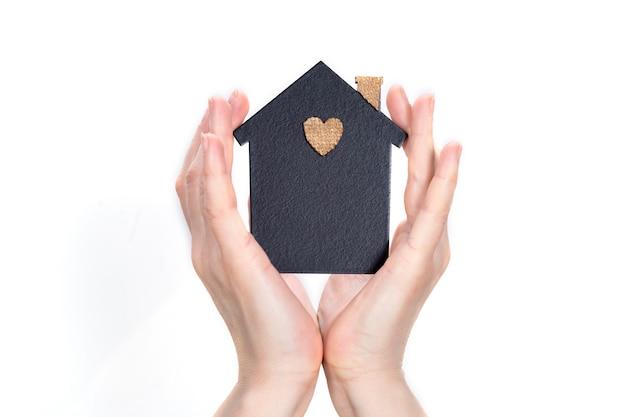 Vrouwelijke handen omringen een model van een donker huis. vastgoed en verzekeringen concept. bescherm uw gezin binnen handbereik