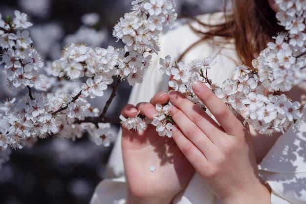Vrouwelijke handen onder de brunch van de bloesemkersenboom in de lentetuin, schoonheid, zomer, emotie, uitdrukking en mensenconcept.