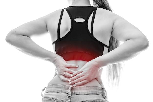 Vrouwelijke handen op de rug die een pijnlijke plek raken