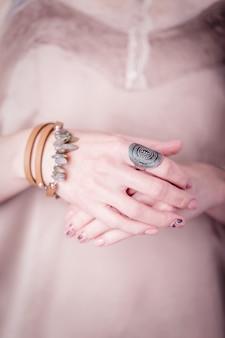Vrouwelijke handen op een licht beige zijden achtergrond met sieraden edelstenen armband en ring